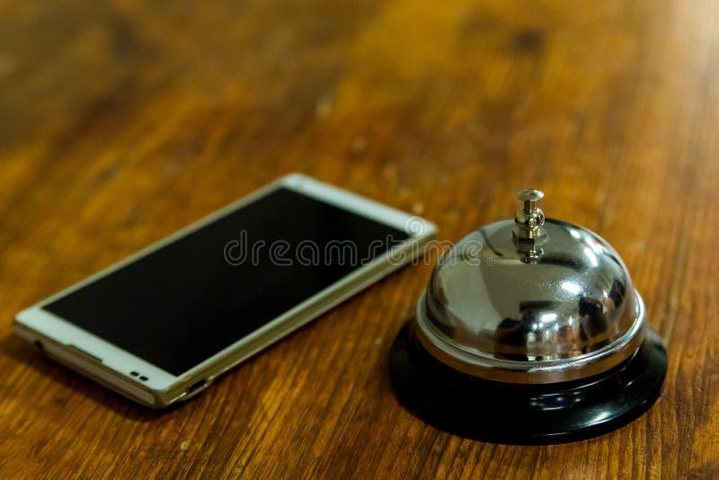 De alarmbel en smartphone van de hoteldienst op houten ontvangstvoorzijde royalty-vrije stock afbeelding