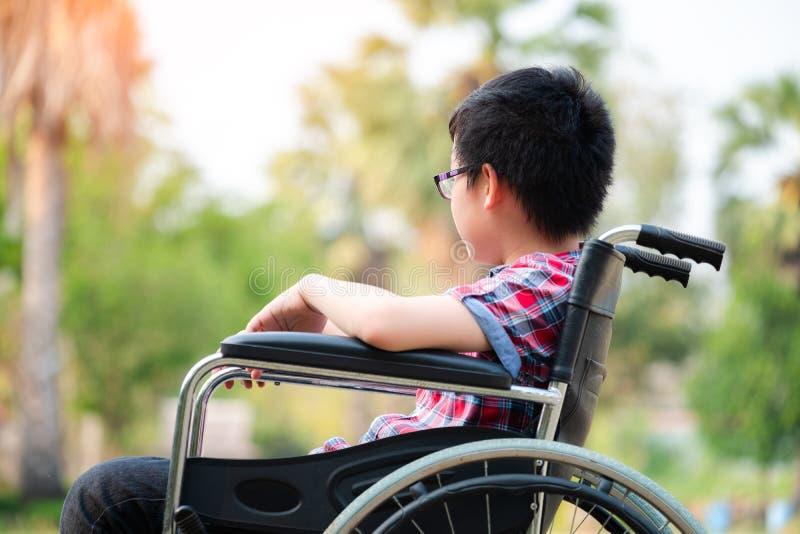 De alleen jonge gehandicapte mens op rolstoel in het park, Patiënt ontspant in tuindecoratie van het het ziekenhuisgevoel van het royalty-vrije stock fotografie