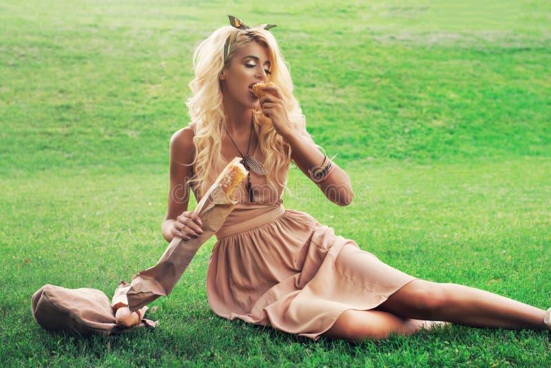 De alleen jonge vrouw die van het schoonheidsblonde in het park rusten stock foto