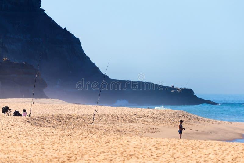 De alleen visser met hengels op het strand probeert zijn geluk als golvenoverlapping op het zand bij Oceaanstrand stock fotografie