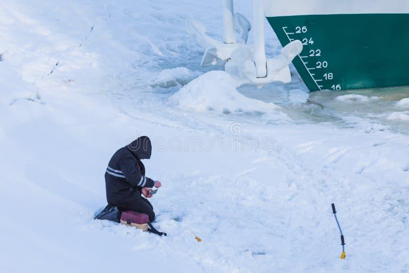 De alleen visserszitting op het ijs en de sneeuw van de de winterrivier op de achtergrond van het schip stock foto