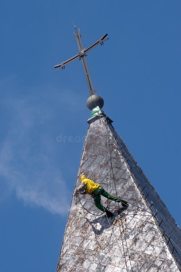 De alpinist maakt kerkdak schoon royalty-vrije stock afbeelding
