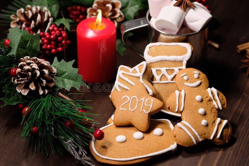 De de amandelkoekjes en koffie met melk in het ijzer vormen op bruine houten achtergrond met Kerstboom tot een kom stock foto