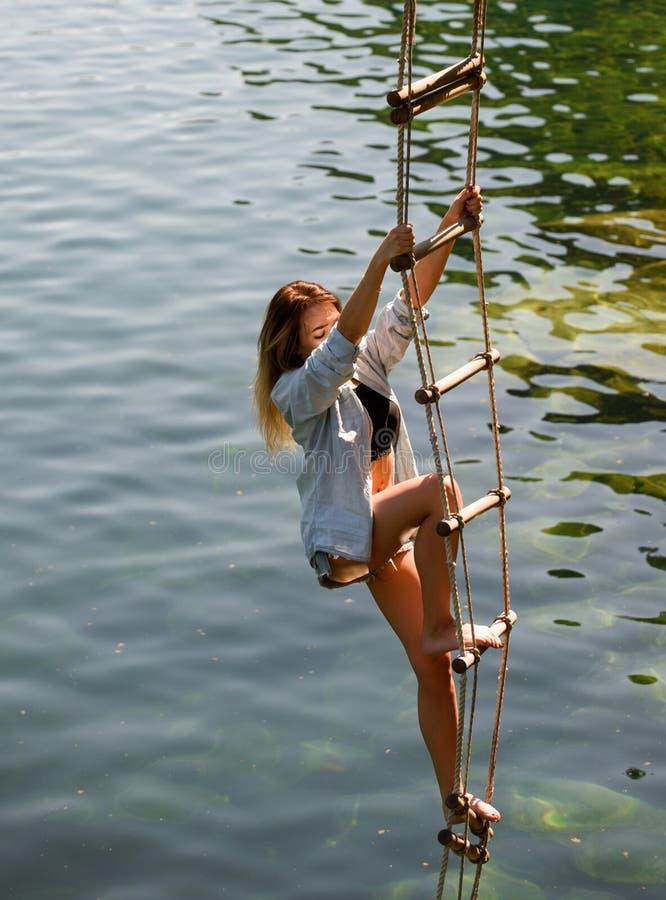 De ambitie kan bergen bewegen vrouw die op touwladder beklimmen De mooie vrouw beklimt jacobs ladder tot de bovenkant Sensueel stock afbeeldingen