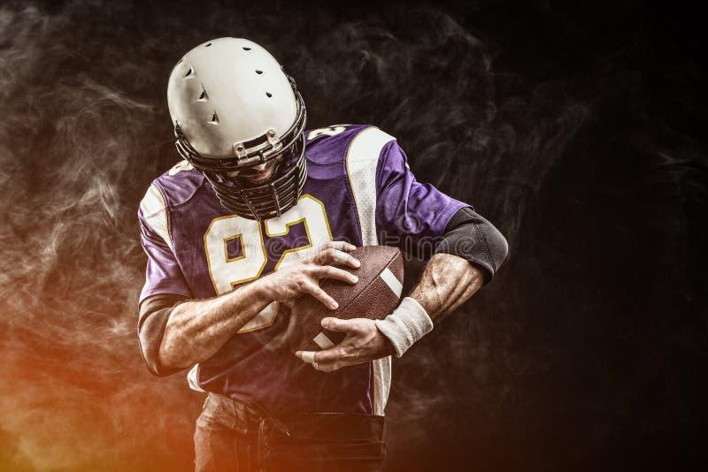 De Amerikaanse bal van de voetbalsterholding in van hem dient rook in zwarte achtergrond, exemplaarruimte Het concept Amerikaan stock foto's