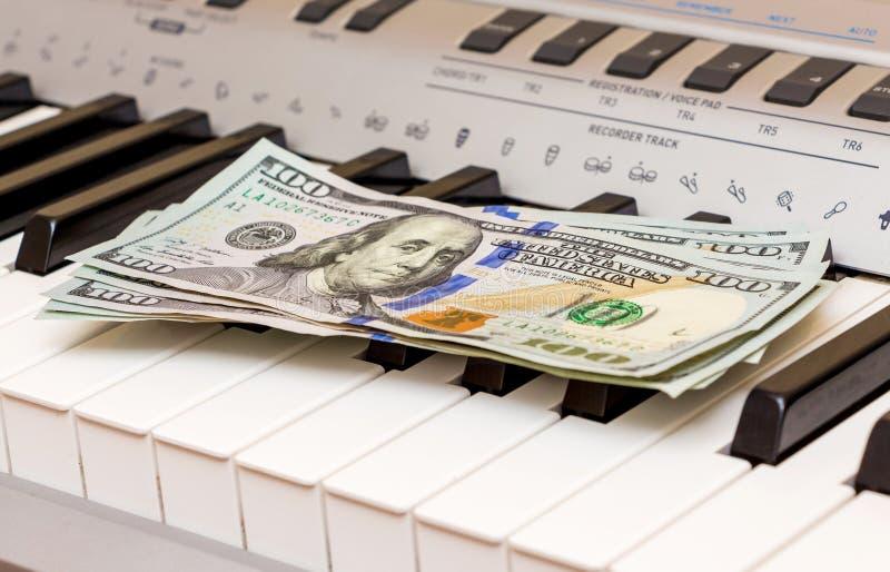 De Amerikaanse dollars liggen op de pianosleutels Betaling voor het overleg, winst van het uitvoeren van musical works_ royalty-vrije stock foto