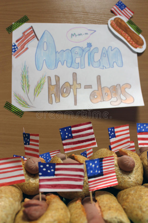 De Amerikaanse hotdogs met kleine Amerikaanse vlaggen sluiten plan, broodje en worst en een inschrijvings Amerikaanse hotdogs op  royalty-vrije stock foto's