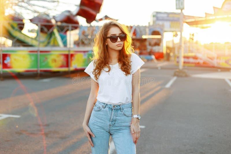 De Amerikaanse modieuze vrouw van roodharige jonge hipster in uitstekende jeans in een modieuze t-shirt in in zonnebril loopt royalty-vrije stock fotografie
