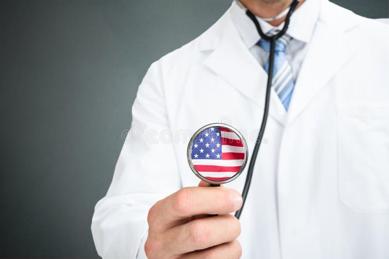 De Amerikaanse Vlag van artsenholding stethoscope with op Chestpiece royalty-vrije stock afbeelding