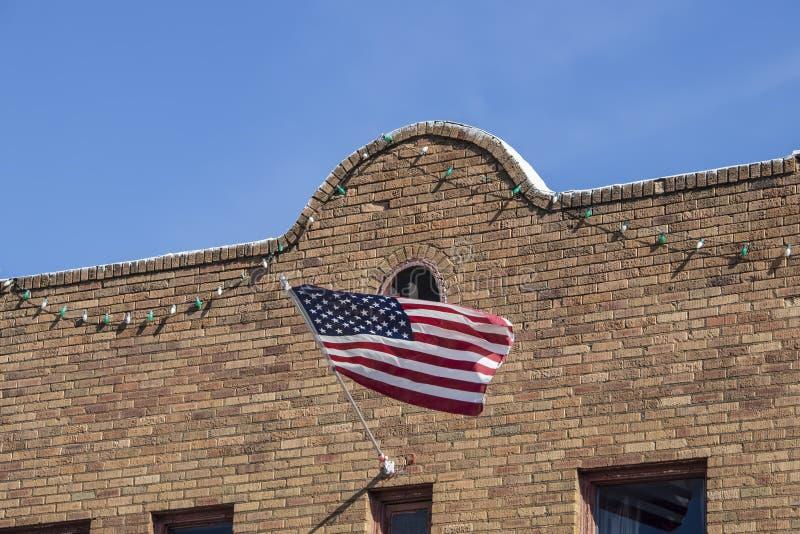De Amerikaanse vlaggolven van retro zuidwestelijke stijlbaksteen de bouwvoorgevel hingen met partijlichten stock afbeelding
