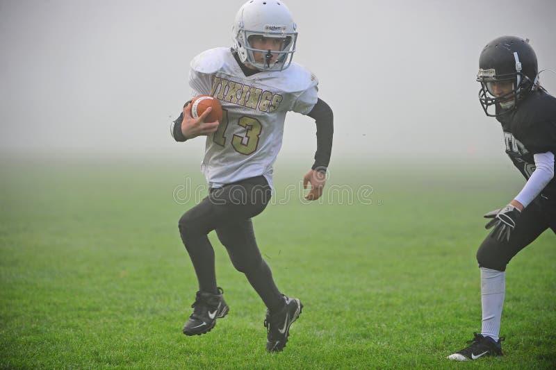 De Amerikaanse Voetbal van de jeugd in de mist stock foto