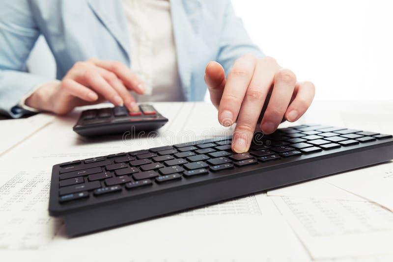 De analyse van effectenbeursgrafieken Bedrijfsvrouw die computertoetsenbord en calculator gebruiken stock fotografie