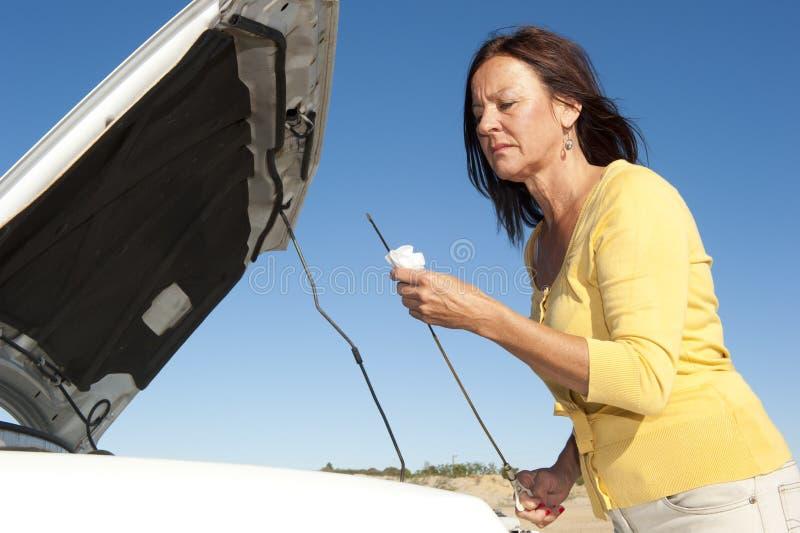 De analysevrouw die van de auto olie controleert stock fotografie