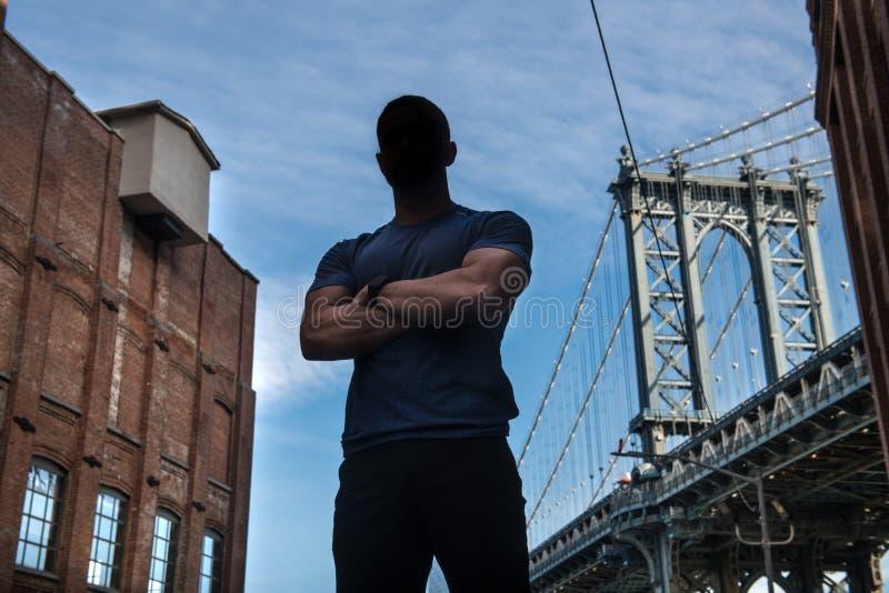 De anonieme atleet van de stadsheld in goede fysieke vorm met gekruiste wapens stelt op stadsstraat stock afbeelding