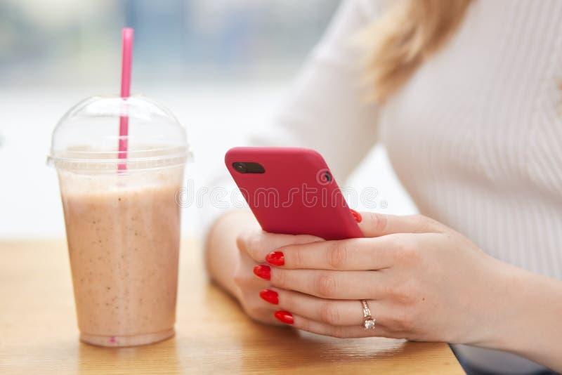 De anonieme vrouw houdt moderne celtelefoon in handen, heeft rode manicure, controleert bericht, drinkt milkshake van plastic kop royalty-vrije stock afbeelding