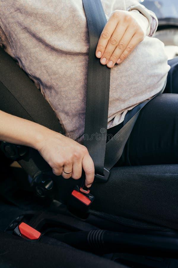 De anonieme zwangere veiligheidsgordel van de vrouwenslijtage in de auto stock foto