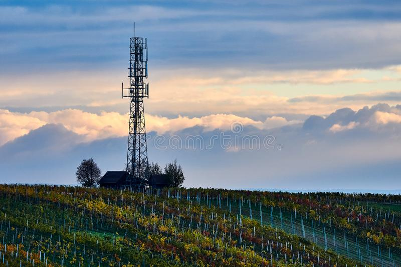 De antenne van de repeater op de achtergrond van de dageraadhemel en de de herfstwijngaarden Zuid- Moravië Tsjechische Republiek stock foto