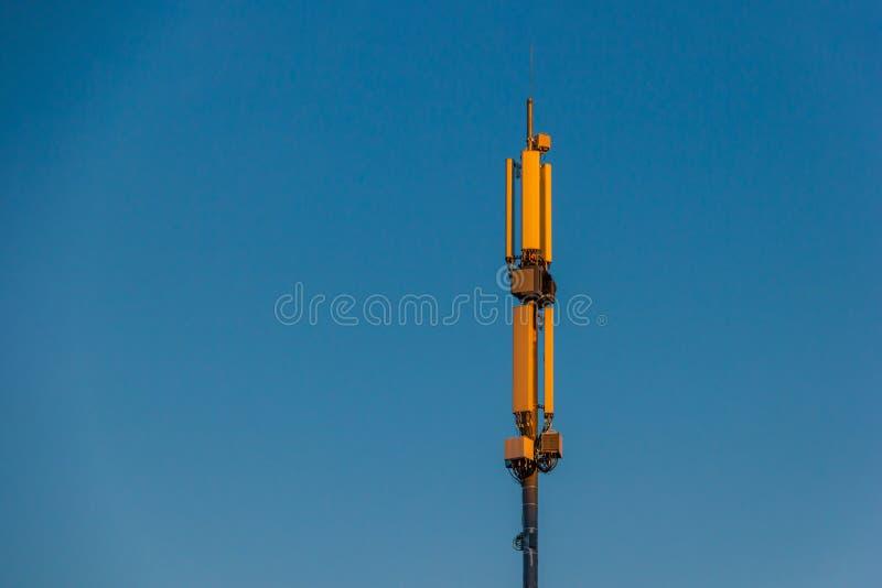 De Antenne van de telecommunicatietoren en satellietschotel bij de achtergrond van de zonsonderganghemel stock foto