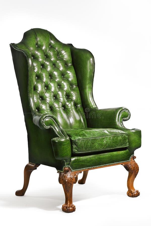 De antieke groene gesneden geïsoleerde benen van de leervleugel stoel stock foto's