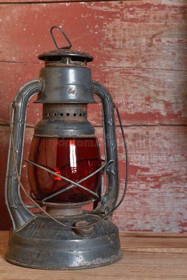 De antieke rode lamp van de glasolie op rode schuurraad stock afbeelding
