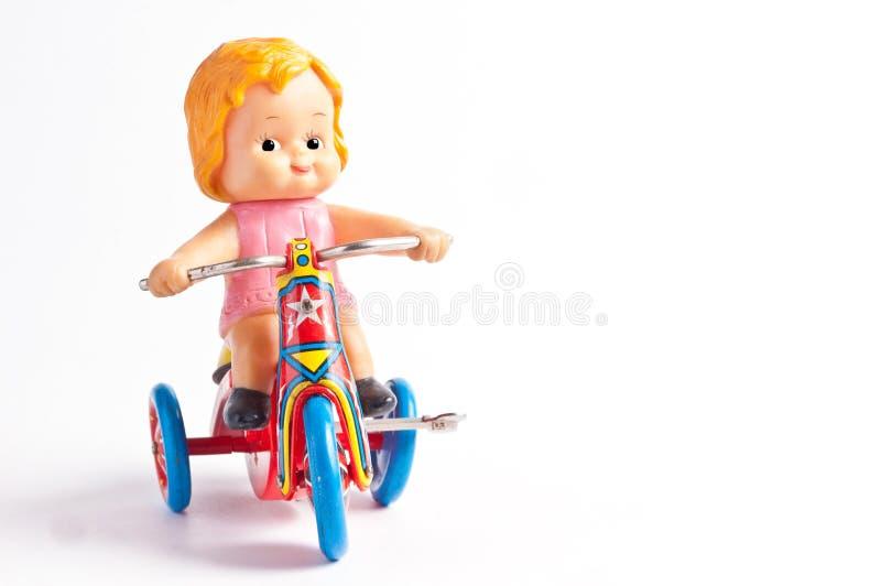 de antieke tinstuk speelgoed fiets van de meisjesrit royalty-vrije stock fotografie