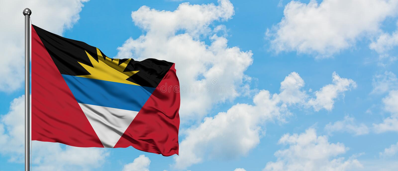De Antigua en Barbuda markeren het golven in de wind tegen witte bewolkte blauwe hemel Diplomatieconcept, internationale relaties stock foto's