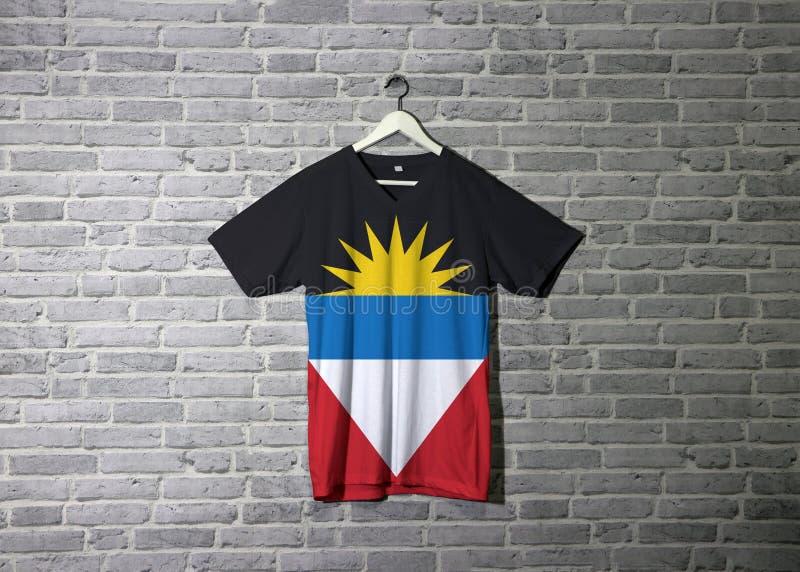 De Antigua en Barbuda markeren op overhemd en het hangen op de muur met het behang van het baksteenpatroon stock foto