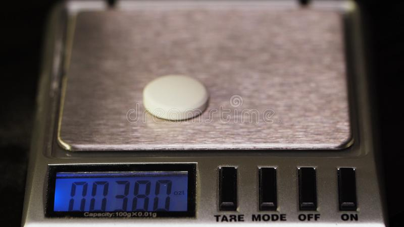 De apotheker, weegt de vervaardigde tabletten op de controleschalen Dieetpillen op een schaal Gemorste de geneeskunde van het gew stock foto's
