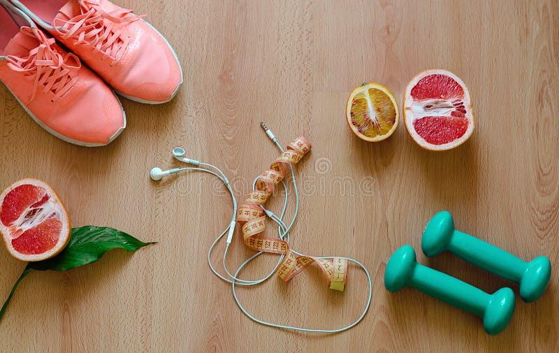 De apparatuur van de geschiktheid Tennisschoenen en natuurlijke voeding op houten achtergrond stock fotografie