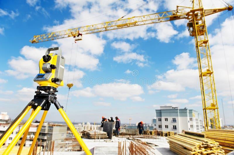 De apparatuur van de landmeter theodoliet bij bouwwerf stock afbeeldingen