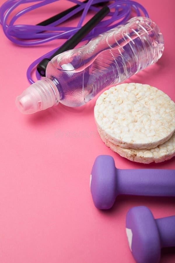 De apparatuur van de geschiktheid Gezond voedsel Giri, springtouw, water en rijstbrood op een roze achtergrond stock foto's