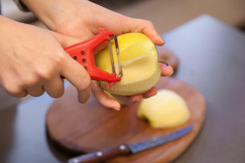 De appel van de handschil met schilmesje stock afbeelding
