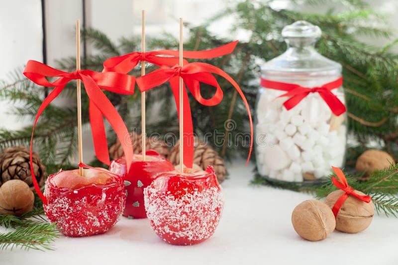 De appelen dompelen in rode van de suikersuikerglazuur en kokosnoot spaanders, Suikergoed, snoepjes en desserts op Kerstmistijd o stock afbeelding