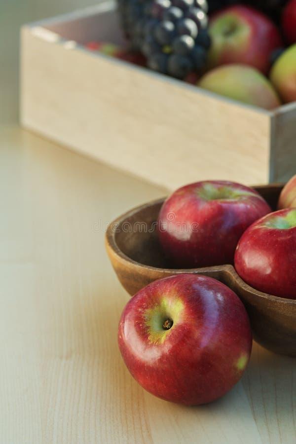 De appelen en de druiven in een houten doos, sluiten omhoog stock afbeeldingen