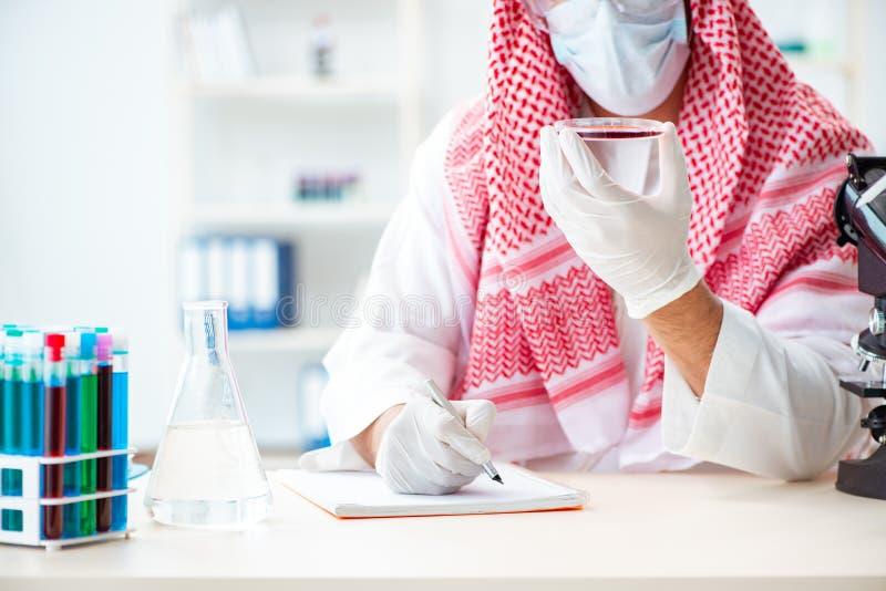 De Arabische artsenchemicus die nieuw virus in laboratorium bestuderen stock afbeeldingen