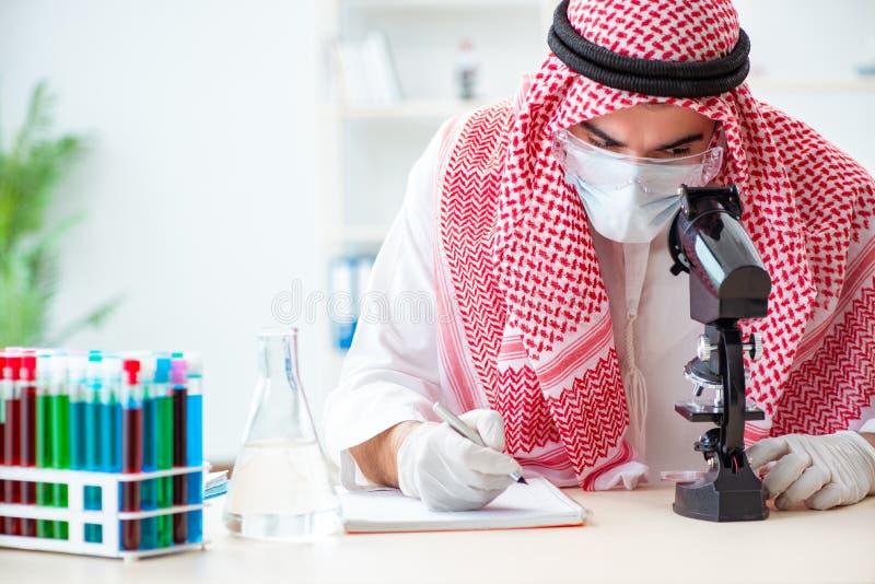 De Arabische artsenchemicus die nieuw virus in laboratorium bestuderen stock fotografie