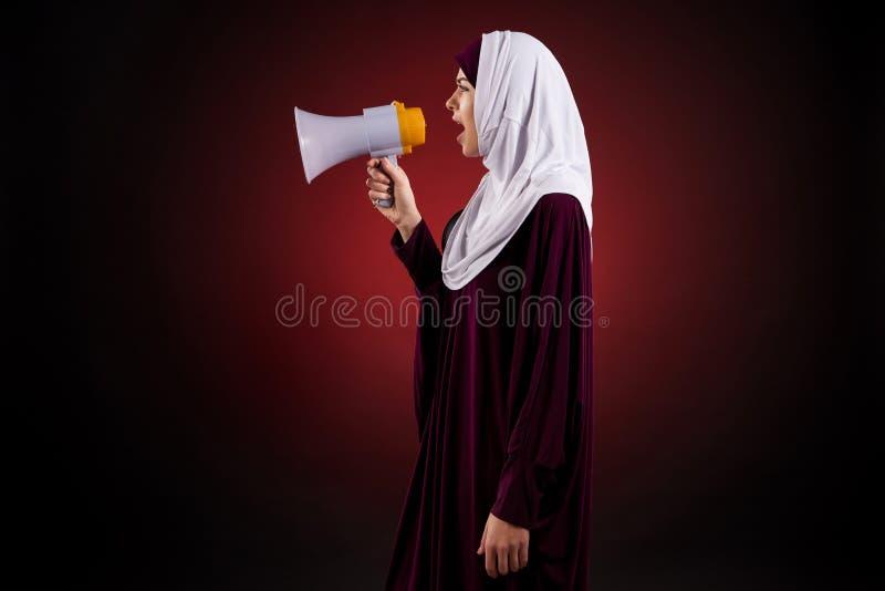 De Arabische jonge vrouw in hijab schreeuwt in megafoon stock afbeeldingen