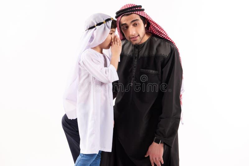 De Arabische jongen vertelt geheim aan vaderoor in keffiyeh royalty-vrije stock foto