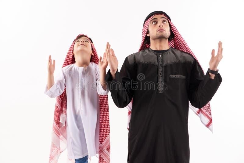 De Arabische vader en de kleine zoon in nationale kledij bidden royalty-vrije stock foto's