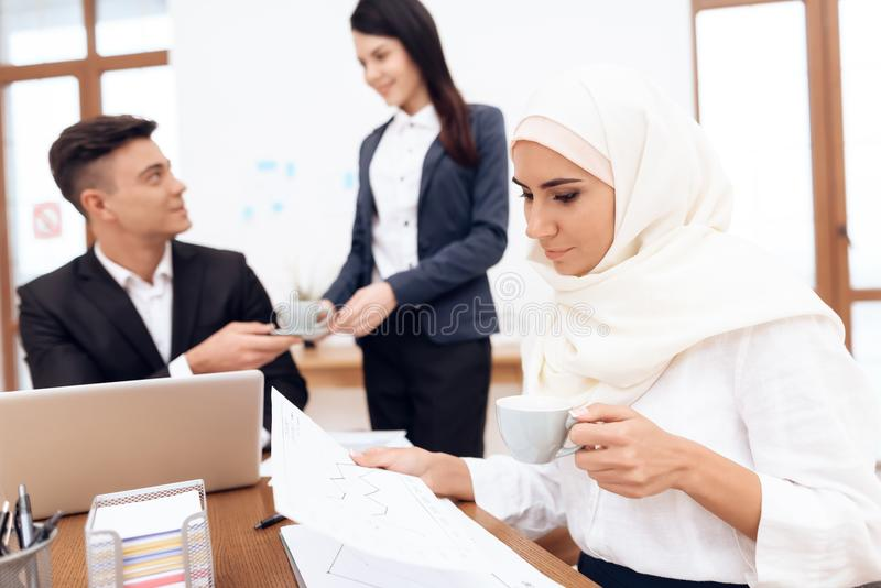 De Arabische vrouw in hijab werkt in het bureau samen met haar collega's royalty-vrije stock foto