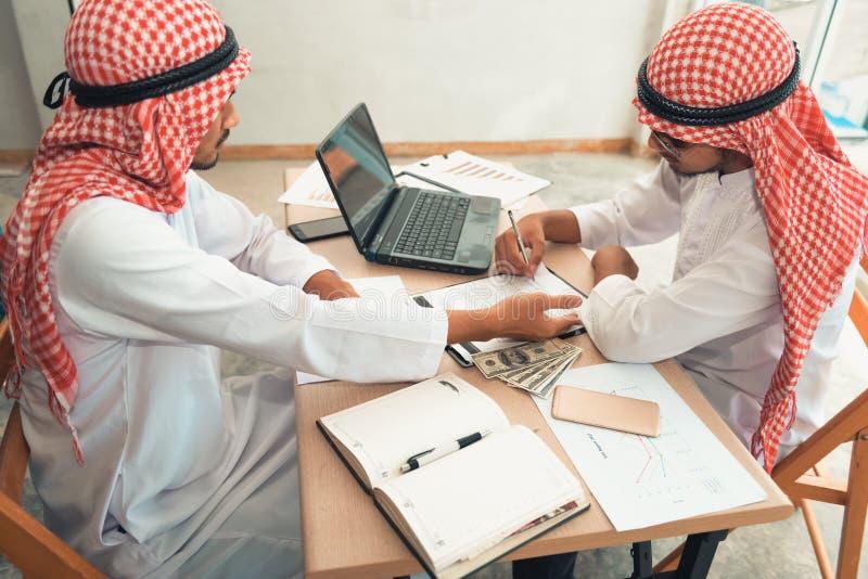 De Arabische zakenlieden ondertekenen contractovereenkomst na succes stock afbeeldingen