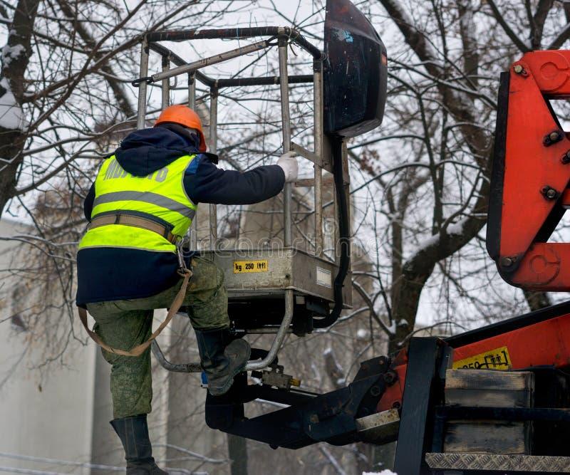 De arbeider beklimt op de lift om het werk uit te voeren stock afbeeldingen