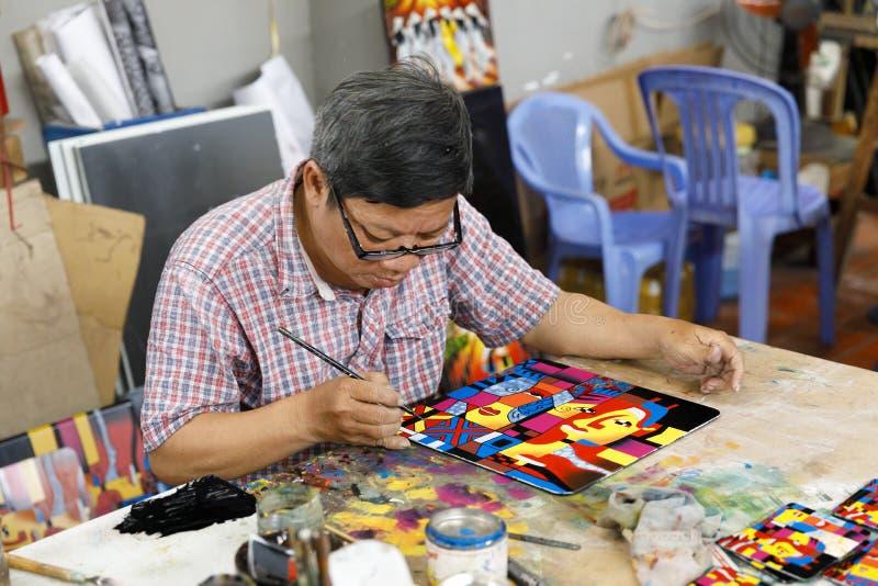 De arbeider creeert het schilderen bij een fabriek in Saigon, Vietnam royalty-vrije stock foto