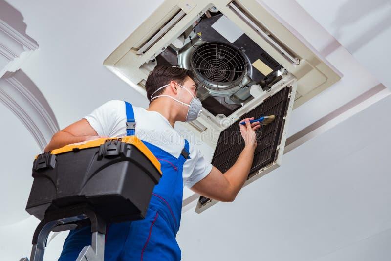 De arbeider die de eenheid van de plafondairconditioning herstellen royalty-vrije stock foto's