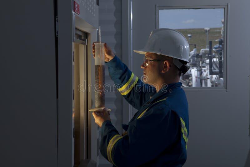 De Arbeider die van de aardolie Chemische producten meet stock foto