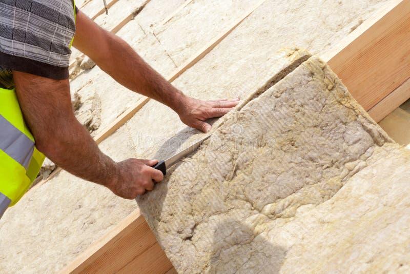 De arbeider die van de Rooferbouwer het materiaal van de dakisolatie in aanbouw installeren op nieuw huis Het snijden rockwall me stock afbeelding