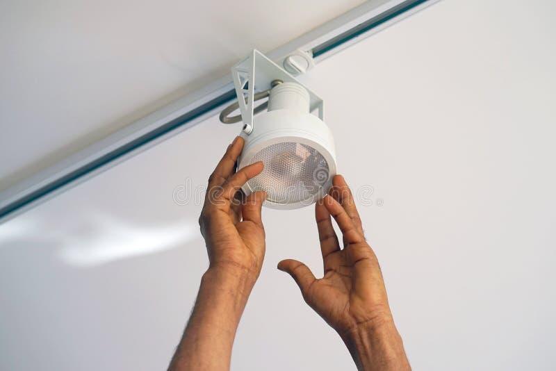 De arbeider die van de elektricienmens een plafond LEIDENE schijnwerper installeren royalty-vrije stock afbeeldingen