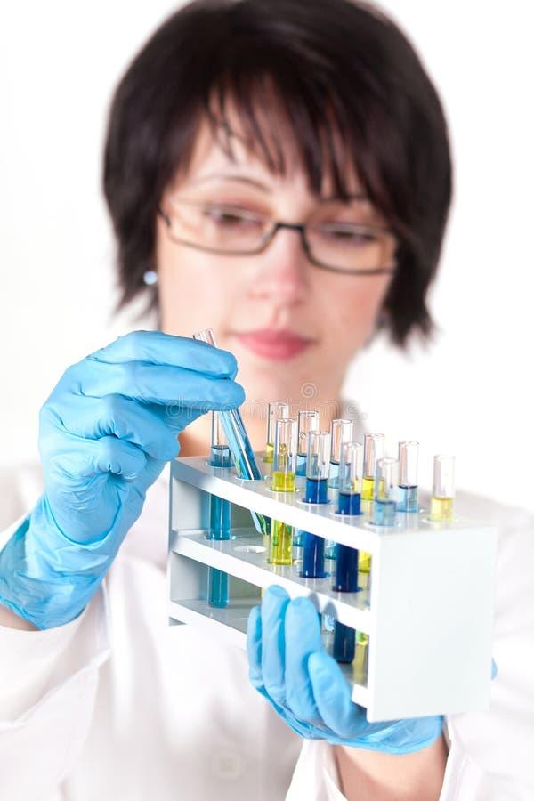 De arbeider die van het laboratorium reageerbuis steunt stock foto