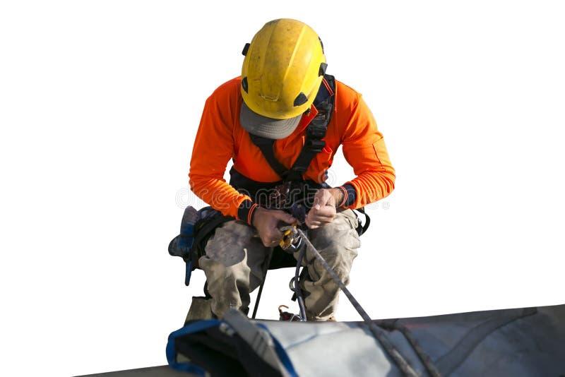 De arbeider die van de kabeltoegang gele bouwvakker, lang kokeroverhemd die, veiligheidsuitrusting dragen, bij hoogte het abseili royalty-vrije stock afbeeldingen