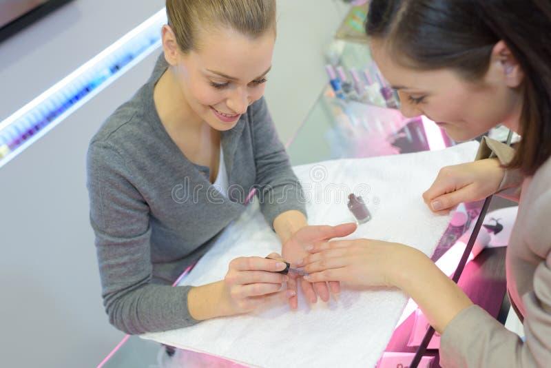 De arbeider die van de spijkersalon manicure geven aan klant stock afbeelding